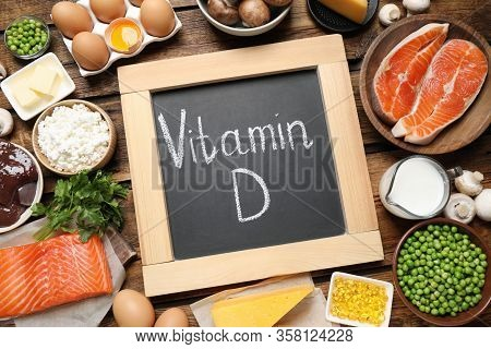 Flat Lay Composition With Products Rich In Vitamin D On Wooden Table