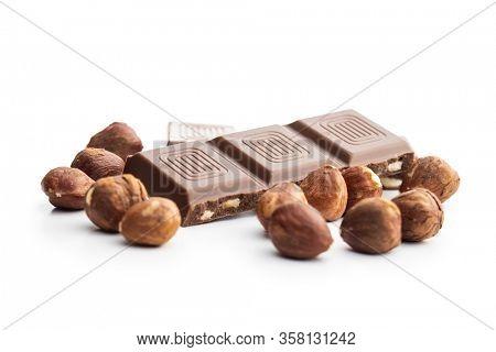 Milk chocolate bars and hazelnuts isolated on white background.