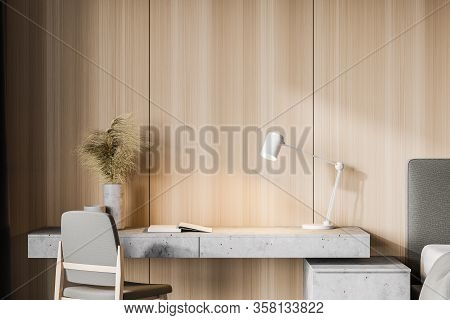 Interior Of Minimalistic Home Office With Wooden Walls, Comfortable Grey Table With Chair And Lamp.