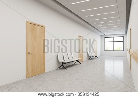 Interior Of Hospital Hallway With White Walls, Concrete Floor, Wooden Doors And Chairs For Visitors.