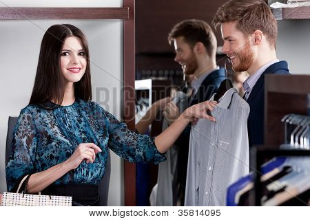 Young man consults with girlfriend while selecting an elegant shirt