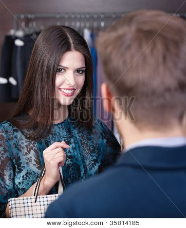 Smiling girl speaks to shop assistant