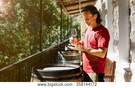 A Handsome Adult Man Stands Near A Wine Barrel On A Farm And Tastes A Glass Of White Wine. Sunny Day