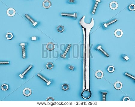 Wrench, Nuts And Bolts On A Blue Background. The View From The Top.