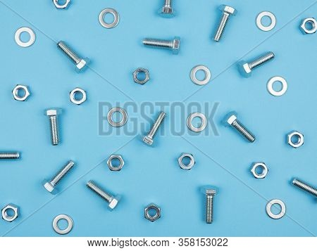 Fastening Elements On A Blue Background. The View From The Top. The Bolts And Nuts.