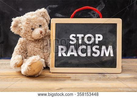 Stop Racism And Kids Concept. Teddy Bear And A Board With Stop Racism Text, School Class Blackboard