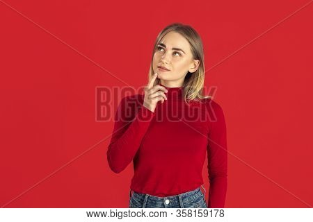 Thoughtful. Monochrome Portrait Of Young Caucasian Blonde Woman Isolated On Red Studio Background. B