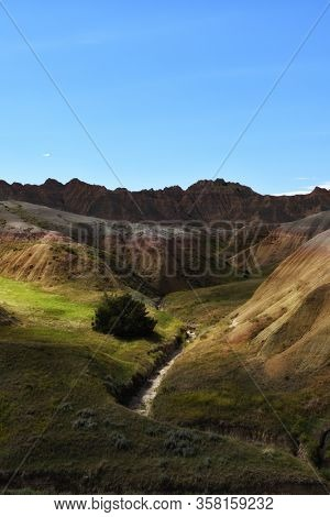 Badlands National Park late afternoon landscape with creek, colorful hills and blue sky.  Vertical orientation.