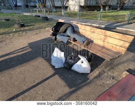 Sleeping Homeless Man On The Wooden Bench. Poverty And Misery Concept.