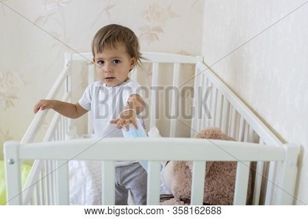 Quarantine Coronavirus Pandemic Concept. A Little Cute Baby Is In Baby Cot At Home In Safety, Lookin