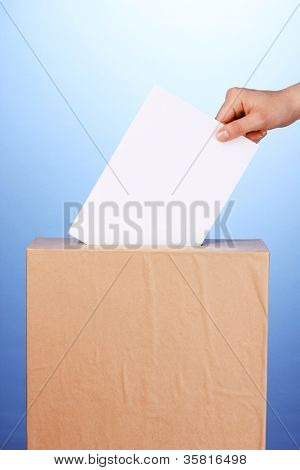 Hand with voting ballot and box on blue background