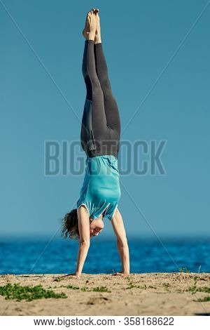 Portrait Of Fit Young Flexible Woman Doing Handstand On The Background Of Blue Sky