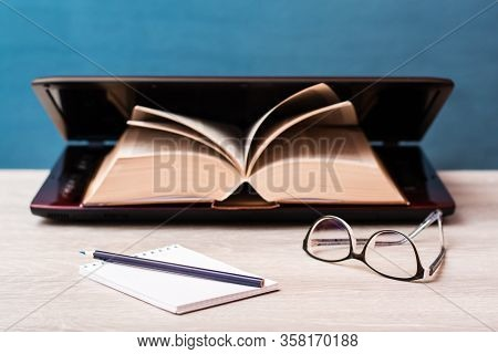 Notebook, Pencil And Glasses On A Background Of A Book In An Open Laptop Table. Distance Learning. T