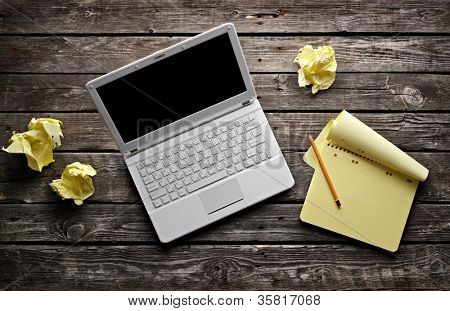 Laptop with blank notepad and pencil with sheets of crumpled paper on old wooden table. Workplace writer or designer.
