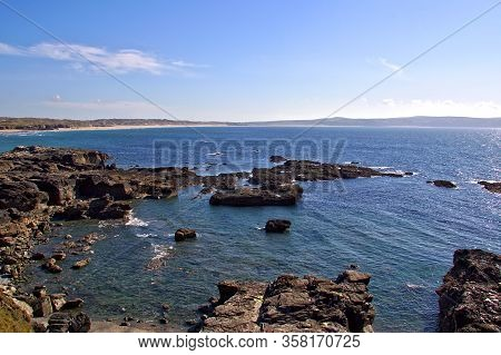 Calm Sea And Rugged Rocks In Late Afternoon