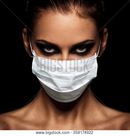 corona virus concept. happy young healthy woman poses in protective mask isolated on black background