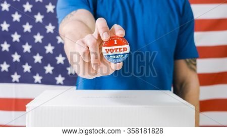 Voting Hand With I Voted Today Button At Box On American Flag.