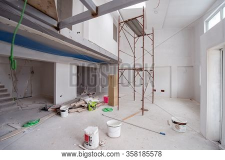 interior of construction site with scaffolding in a large modern unfinished duplex apartment