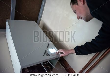 Maintenance engineer checking technical data of heating system equipment in a boiler room. Plumber installing pressure meter for house heating system