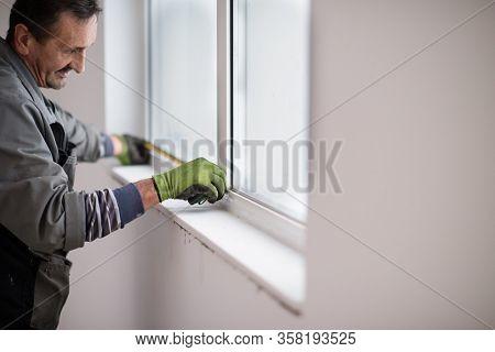 service man installing window with measure tape Man measuring window before installation of roller shutter