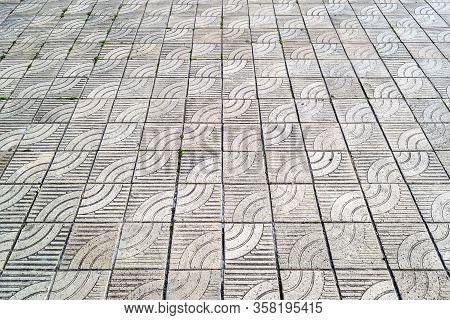 Texture Of Gray Square Concrete Paving Slabs With A Stylized Wave Ornament. Paving Slabs With A Diag