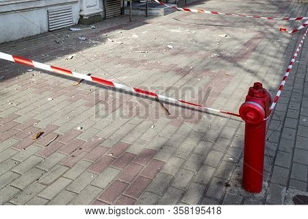 Red White Signal Tape Encloses A Part Of The Sidewalk With Construction Debris During The Repair Of