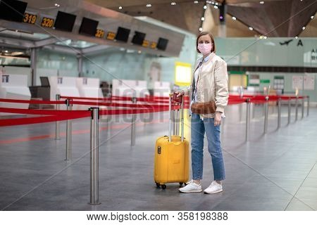 Woman With Luggage Stands At Almost Empty Check-in Counters At The Airport Terminal Due To Coronavir