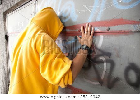 Young man in hooded sweatshirt / jumper facing grunge graffiti wall. Conceptual
