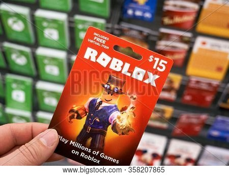 Montreal, Canada - March 22, 2020: Roblox Gift Card In A Hand Over Gift Cards Background. Roblox Is