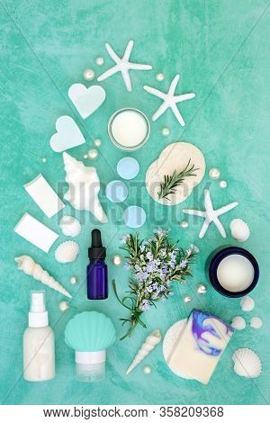 Skincare beauty treatment with fresh rosemary herb and cosmetic products. With astringent & anti ageing benefits & helps to reduce environmental skin damage. Flat lay on turquoise.