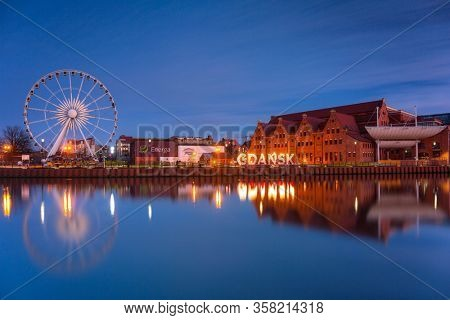 Gdansk, Poland - March 19, 2020: Gdansk with beautiful ferris wheel over Motlawa river at dusk, Poland.