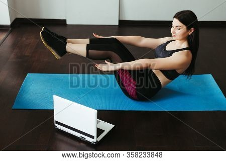 Sport, Home Training, Online Fitness Class. Young Fit Woman Doing Sit-ups On Mat At Home Looking Vid