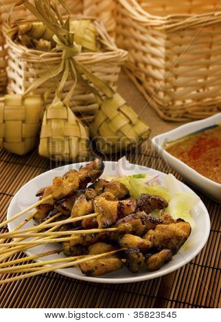 Asian Malay Ramadan food, satay chicken and ketupat in low light poster