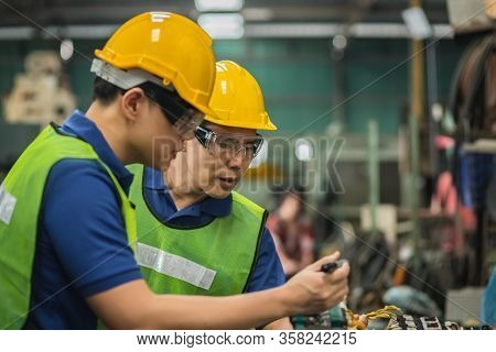 Two Men Engineer Talking In Modern Factory. Production Line Machine And Setting It For Work.
