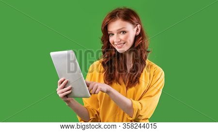 Cheerful Student Girl Using Digital Tablet Browsing Internet Standing On Green Studio Background. Pa