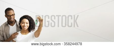 African American Young Smiling Couple Showing Keys Of New Home On White Background