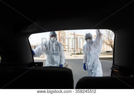 Men In Virus Protective Suits Looking Into The Trunk Of Car Outdoor, Covid 19 Epidemic, Copy Space