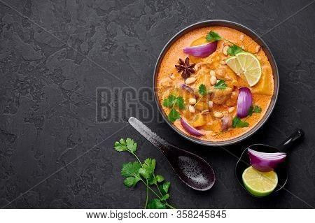 A Chicken Massaman Curry In Black Bowl At Dark Slate Background. Massaman Curry Is Thai Cuisine Dish
