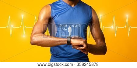 Fit Concept. Black Muscular Man Checking Fitness Tracker, Yellow Studio Wall, Panorama, Heart Beat L