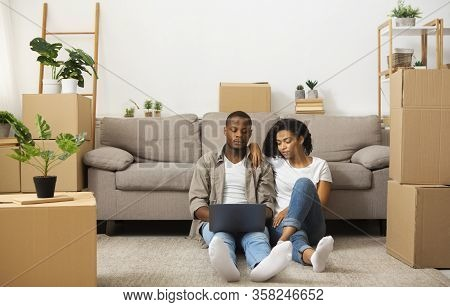 Room Design Ideas Concept. African American Couple Sitting On Floor With Laptop