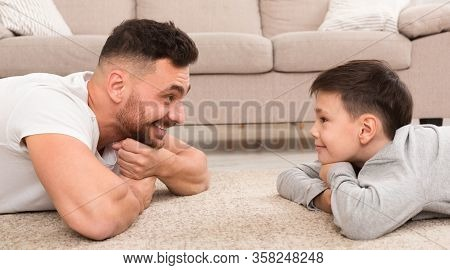 Stay At Home. Cute Boy And Handsome Man Looking At Each Other, Lying On Floor At Home, Panorama