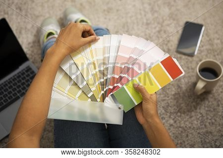 African American Millennial Girl Chooses Paint For Interior From Color Swatch, Cropped