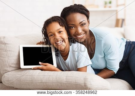 Check This Out. Black Kid With Mom Holding Digital Tablet, Showing Screen, Introduce App Or Favorite