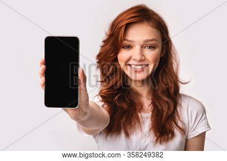 Mobile App. Smiling Ginger-haired Girl Showing Cellphone Blank Screen Recommending Application On Wh