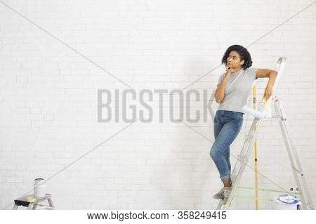 African American Millennial Female Coloring Wall With Paint Roller, Free Space