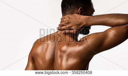 Unrecognizable Athlete Man Having Neck Pain Standing On White Studio Background. Back View, Panorama