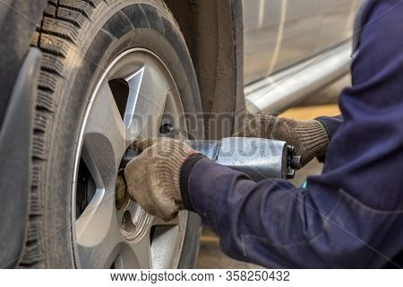 Hands Of Automotive Mechanic Unscrewing Nuts With Pneumatic Impact Wrench During Car Wheels Season C