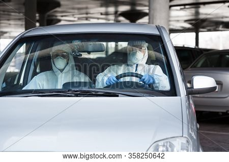 Medical Worker And Virologist In Protective Suits Driving A Car, World Pandemic, Coronavirus Epidemi
