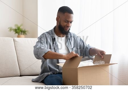 African American Male Buyer Unpack Cardboard Box At Home