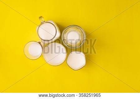 Group Glass Of Milk On Yellow Background With Copy Space, View From Above Table.
